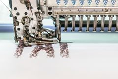 Computerized embroidery machines. sewing machine on blurred background. textile workshop. closeup.  royalty free stock photography