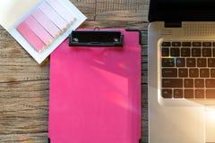 Computerlaptop en de roze klembord en kleverige nota over werkende lijstvlakte leggen samenstellings hoogste mening met exemplaar royalty-vrije stock foto