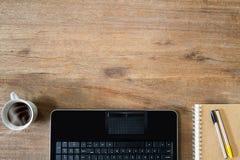 Computerlaptop, Kaffeetasse, Notizbuch und Stifte auf hölzernem Schreibtisch des Weinleseschmutzes Lizenzfreies Stockfoto