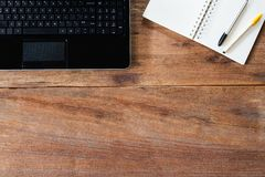 Computerlaptop, -notizbuch und -stifte auf hölzerner Tischplatte der Schmutzweinlese Lizenzfreie Stockfotografie