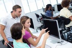 Computerleraar die vrij vrouwelijke studenten helpen royalty-vrije stock foto's