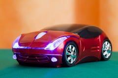 Computermaus im roten Sportauto des Formularspielzeugs Stockfoto