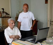 An older man 88 years works on a laptop and a younger man 60 years old checks him stock photography