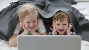 Computers in het leven van moderne kinderen weinig broer en zuster het letten op beeldverhalen op laptop, die op bed binnen ligge stock videobeelden