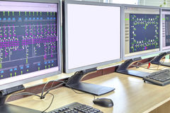 Computers and monitors with schematic diagram for supervisory, control and data acquisition. In modern electrical control room royalty free stock image