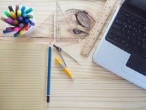 Computers, potloden, notitieboekjes en tekeningshulpmiddelen op houten raad Betekenis van het ontwerpwerk stock foto