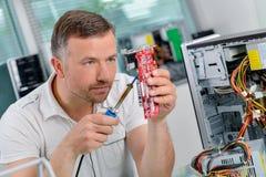 Computerspezialist, der gedruckte Schaltung repariert stockbild