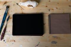 Computertablette auf dem Holztisch nahe bei dem Schädel eines Fuchses Kreative kreative Männer des Arbeitsplatzes Lizenzfreie Stockfotos