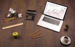 Computertisch mit Laptop und rotes Pfeildiagramm auf Schirm Stockfotografie