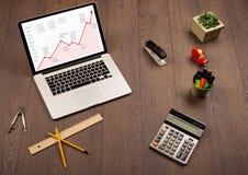 Computertisch mit Laptop und rotes Pfeildiagramm auf Schirm Lizenzfreies Stockfoto