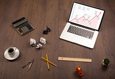 Computertisch mit Laptop und rotes Pfeildiagramm auf Schirm Lizenzfreie Stockfotos