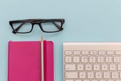 Computertoetsenbord, glazen en notitieboekje op de blauwe werken als achtergrond Royalty-vrije Stock Foto