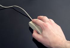 Computing. Man's hand holding computer mouse, black reflective background Stock Photo