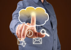 Computing concept. Close up of businessman touching cloud icon with finger Stock Images
