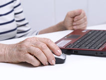 Computing. Elderly person's hand on a mouse Royalty Free Stock Photo