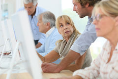 Computing training of seniors with instructor. Group of senior people attending computing class Stock Photos