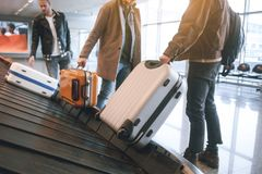 Comrades holding baggages in hall. Low angle male friends putting luggages while standing in airport. Journey concept Stock Image