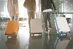 Comrades holding baggages in hall. Three male friends keeping luggages while going in airport. Trip concept Royalty Free Stock Images