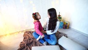 Comunicación de una más vieja hermana femenina con la muchacha más joven que se sienta en piso en sitio en el fondo de la pared c metrajes
