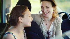 Comunicación emprendedora y amistosa entre la madre y la hija con un adolescente El sentarse junto dentro del coche almacen de metraje de vídeo