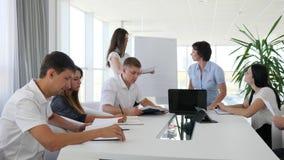 Comunicación empresarial de colegas en la tabla en el trabajo en oficina moderna almacen de video