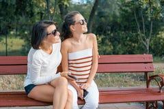 Comunicación entre el padre y el niño Adolescente de la mamá y de la hija que habla y que ríe mientras que se sienta en el banco  imágenes de archivo libres de regalías