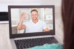 Comunicación video con el amigo en el ordenador portátil del hogar imagen de archivo
