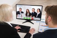 Comunicación video de dos empresarios en el ordenador imagen de archivo libre de regalías