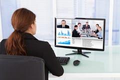 Comunicación video de la empresaria con el equipo en el ordenador Fotos de archivo