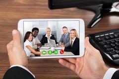 Comunicación video del empresario en el teléfono móvil fotos de archivo