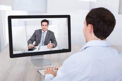 Comunicación video del hombre de negocios con el compañero de trabajo en la PC en el escritorio imagenes de archivo
