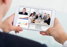 Comunicación video del hombre de negocios con el equipo en la tableta digital fotos de archivo