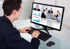 Comunicación video del hombre de negocios con el equipo en oficina imágenes de archivo libres de regalías
