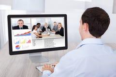 Comunicación video del hombre de negocios con los colegas en la PC en el escritorio imagen de archivo