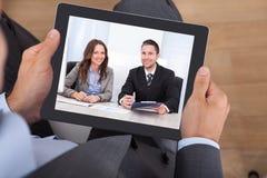 Comunicación video del hombre de negocios con los colegas en la tableta digital imágenes de archivo libres de regalías