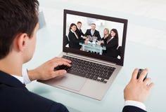 Comunicación video del hombre de negocios en el ordenador portátil en oficina Imagenes de archivo