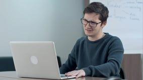 Comunicación video del muchacho joven con el profesor particular en el ordenador portátil en escuela Fotos de archivo libres de regalías
