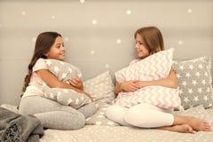 Comunicaci?n de las hermanas Las hermanas comunican rato para relajarse en dormitorio Tiempo de la familia Los ni?os se relajan y imagen de archivo libre de regalías