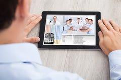 Comunicación video del hombre de negocios con el equipo médico Imagenes de archivo