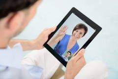 Comunicación video del skype sobre ipad de la manzana Imágenes de archivo libres de regalías