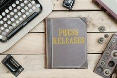 Comunicado de imprensa na capa do livro velha na mesa de escritório com o artigo do vintage fotos de stock royalty free
