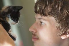 Comunicando-se com um animal de estimação, o gatinho olha o proprietário Imagem de Stock