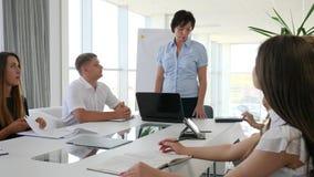 Comunicazione commerciale alla tavola di giovani collaboratori con i documenti in mani in ufficio stock footage