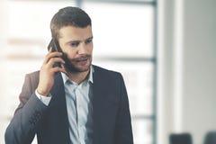 Comunicazione commerciale - giovane uomo d'affari che parla sul telefono immagini stock libere da diritti