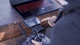 Comunicazione con quadcopter clip Primo piano dell'uomo che installa collegamento con quadcopter tramite il telefono con la ripre video d archivio