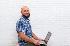 Comunicazione online di affari dell'uomo di seduta del computer portatile barbuto casuale della tenuta Fotografia Stock Libera da Diritti