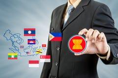 Comunidad económica de la Asociación de Naciones del c@sureste Asiático en mano del hombre de negocios Foto de archivo libre de regalías