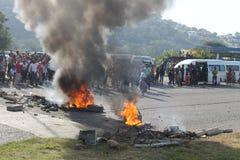 Comunidad que efectúa una protesta que bloquea un camino durante una huelga del taxi en Durban Suráfrica Fotos de archivo