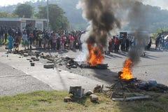 Comunidad que efectúa una protesta que bloquea un camino durante una huelga del taxi en Durban Suráfrica Imagenes de archivo