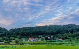 A comunidade de exploração agrícola sob um céu azul encheu-se com a nuvem branca inchado imagem de stock royalty free